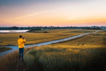 Mann mit gelber Jacke fotografiert Landschaft in Roskilde