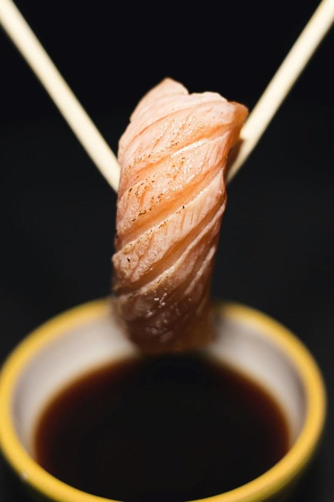 Sushi wird mit Holzstäben in Sojasauße getunkt