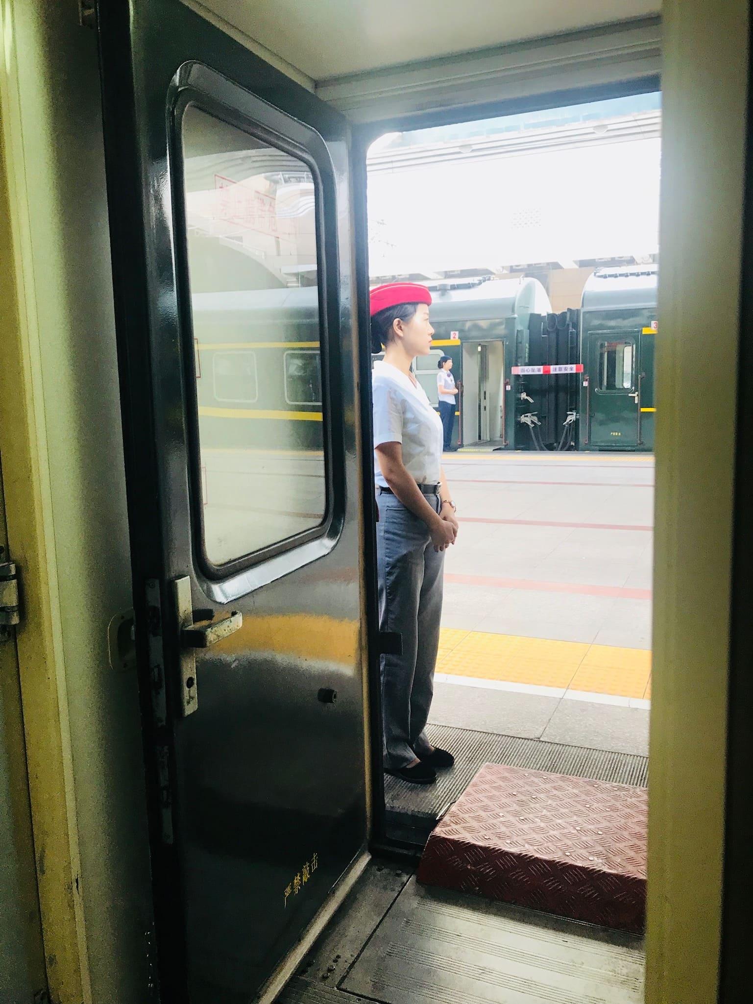 Schaffnerin steht vor Zug in Guangxi in China