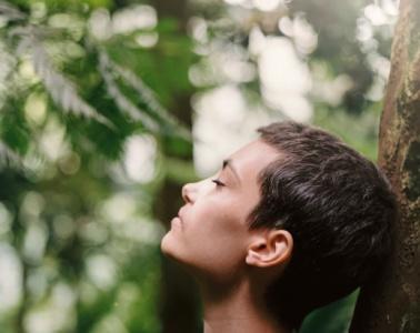 Frau steht mit geschlossenen Augen im Wald und atmet tief durch