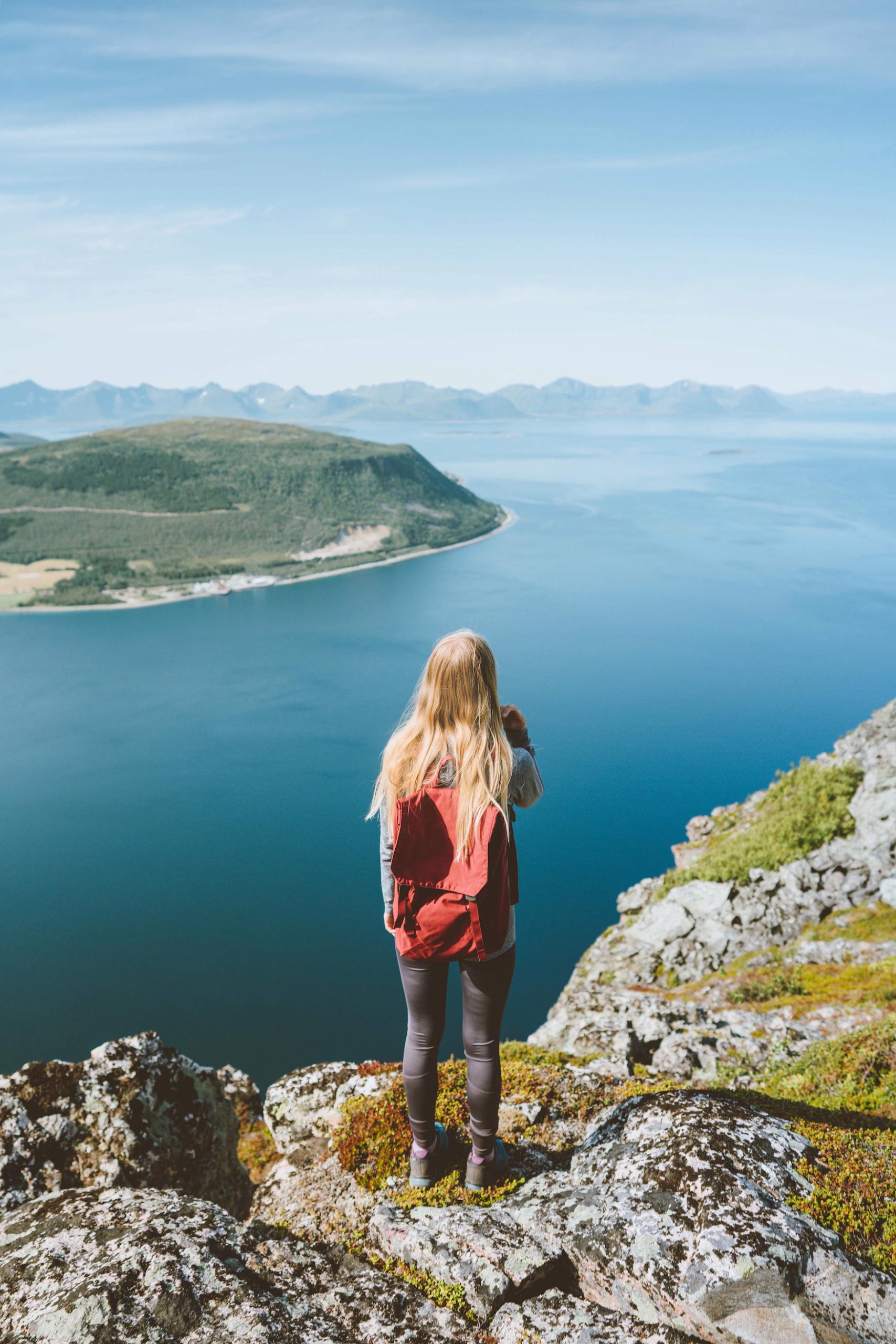 Mädchen mit rotem Rucksack steht vor Fjorden in Norwegen
