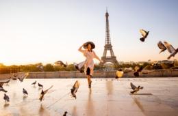 Frau posiert in die Kamera vor Eiffelturm in Paris während Sonnenuntergang