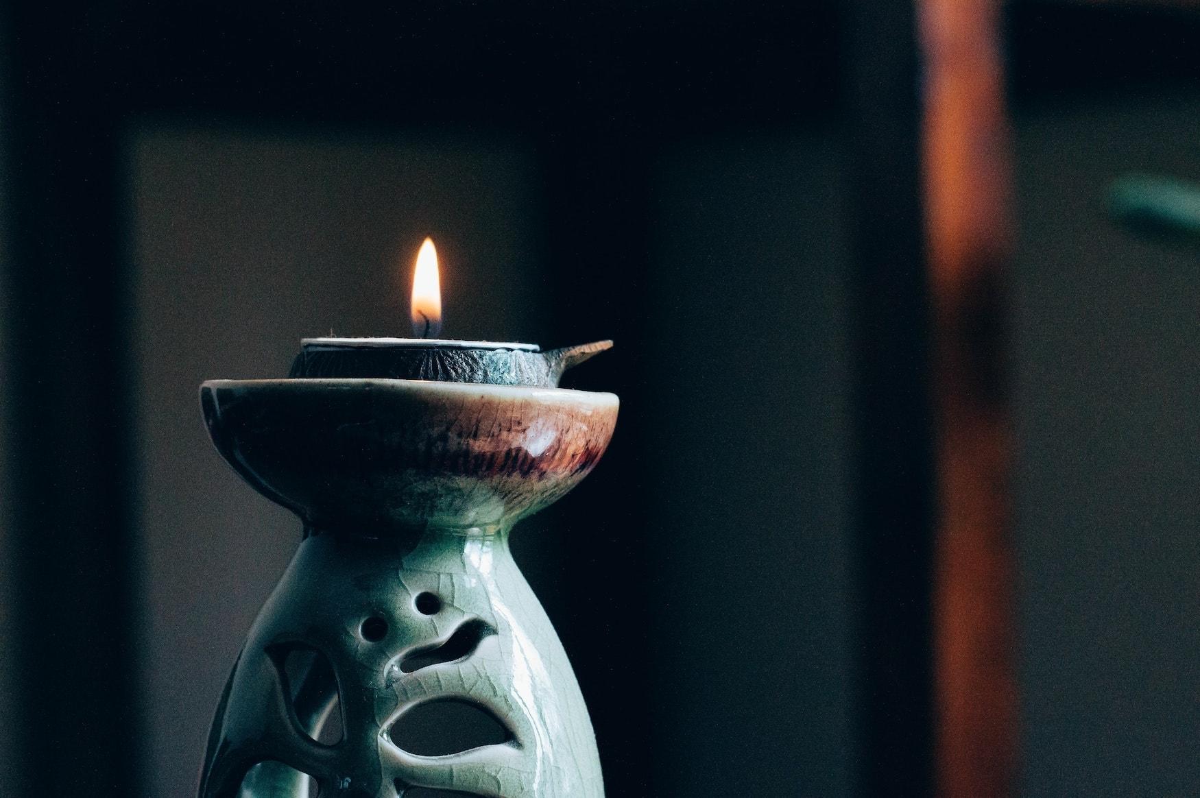 Leuchtende Kerze vor dunklem Hintergrund