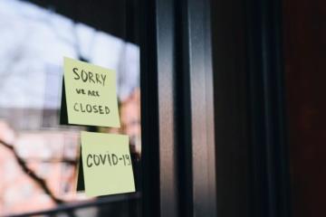 """Zwei Zettel mit den Aufschriften """"Sorry, we are closed"""" und """"Covid 19"""" hängen an einer Glassscheibe"""