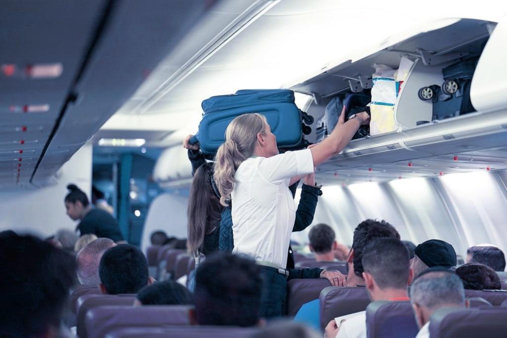 Flugbegleiterin hilft dabei, Koffer im Handgepäckfach zu verstauen