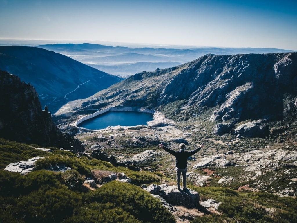 Mann breitet die Arme aus und blickt auf die Landschaft im Serra da Estrela