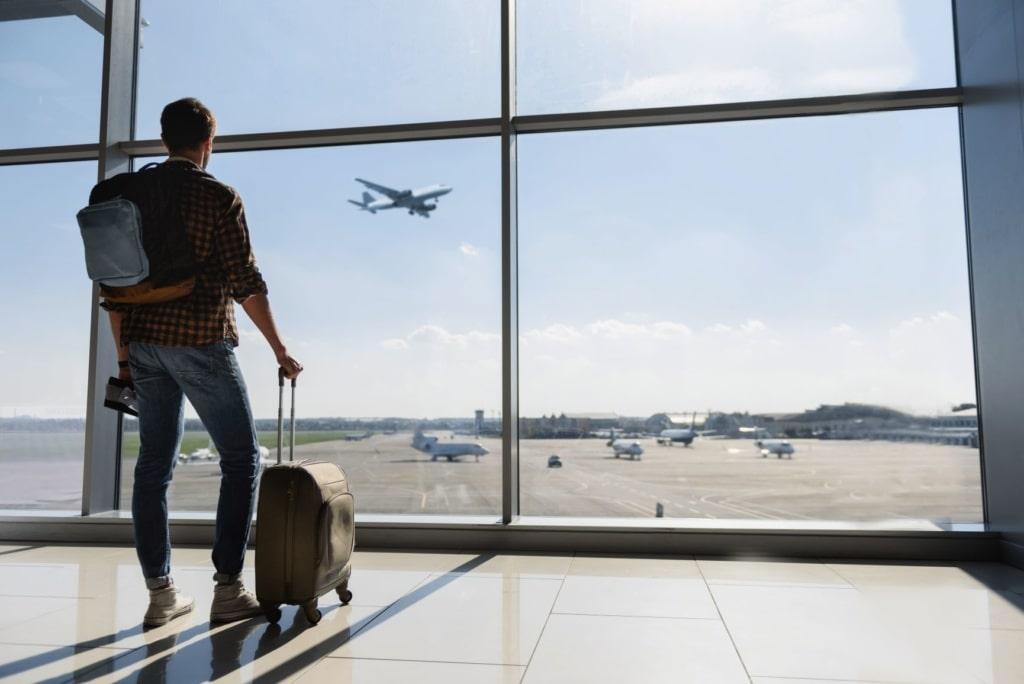Mann steht im Flughafen mit Trolley und beobachtet Rollfeld