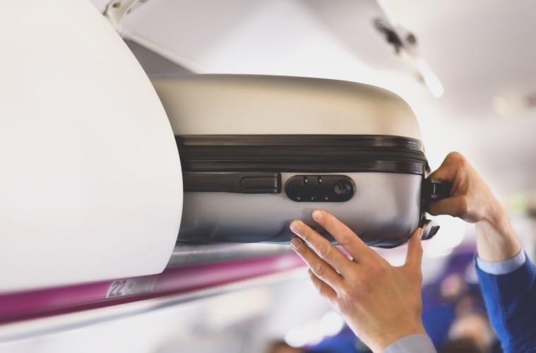 Mann schiebt Koffer in Ablagefläche im Flugzeug