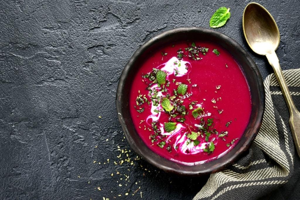 Rote-Beete-Suppe auf schwarzem Tisch-Untergrund