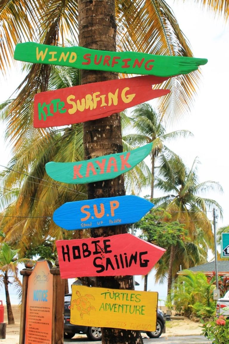 Sportangebote auf bunten Holzschildern am Pigeon Point in Tobago