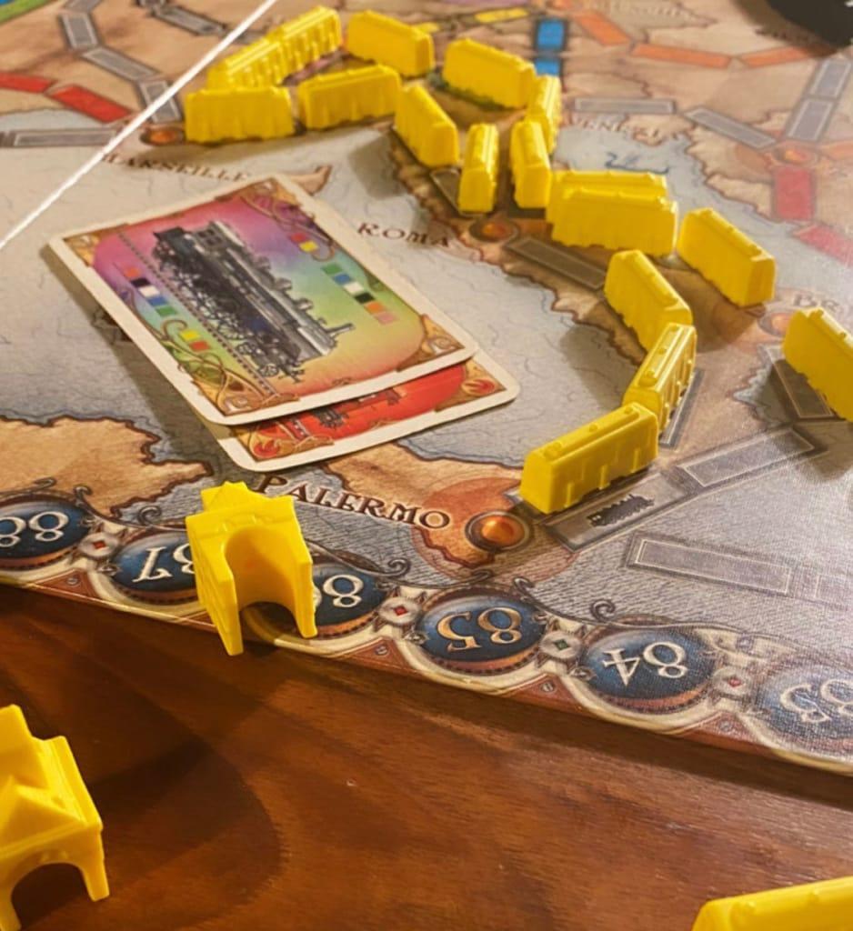 Brettspiel Zug um Zug mit gelben Zügen und Spielkarte
