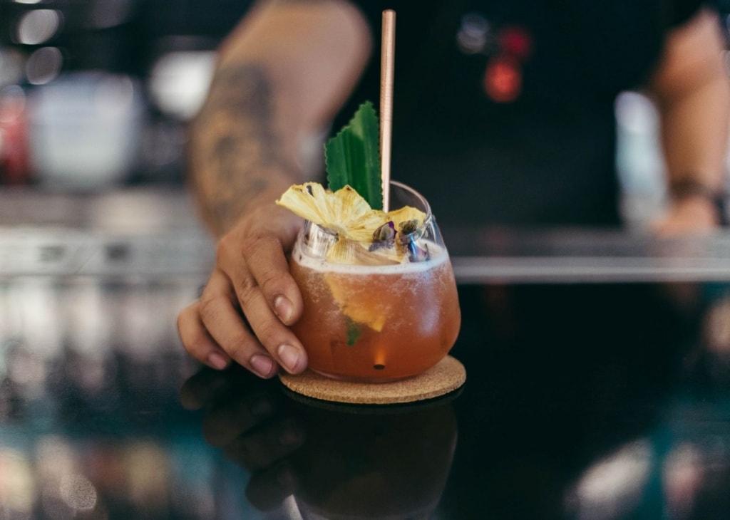 Hand stellt Cocktail auf Tisch