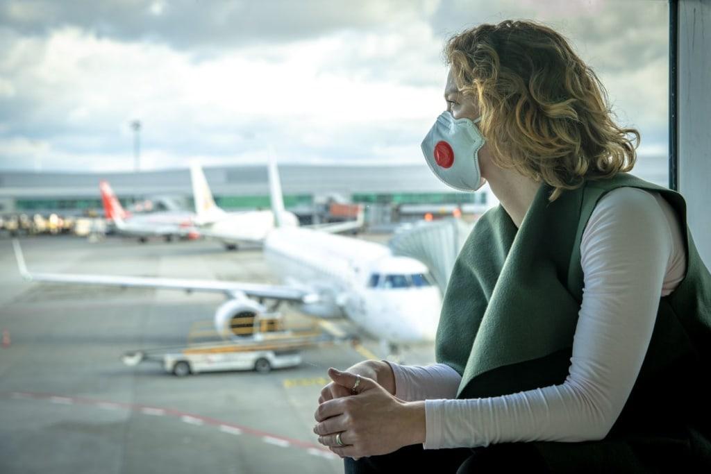 Besser mit Reiserücktrittsversicherung: Frau mit Corona-Schutzmaske blickt auf Airport-Rollfeld
