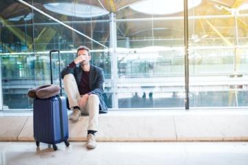 Mann sitzt am Flughafen und ist wegen Reiserücktritt verzweifelt