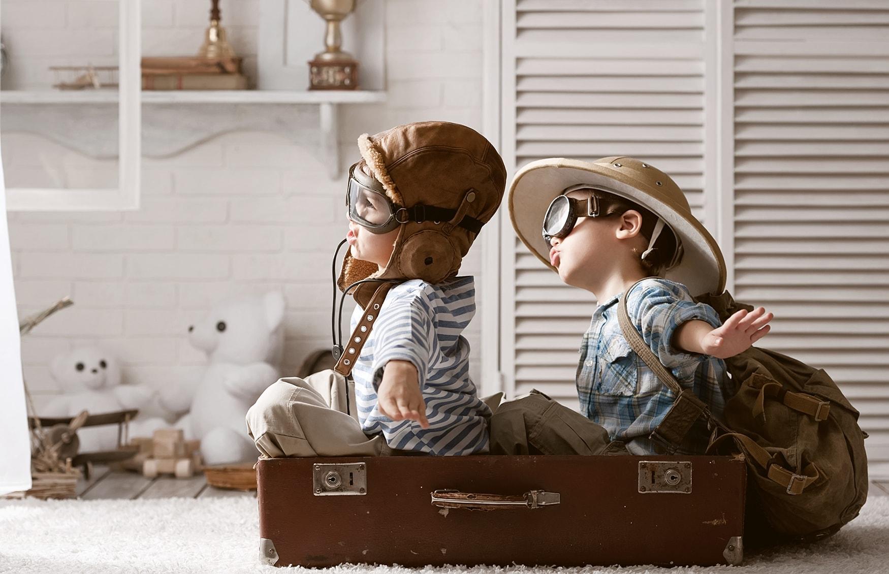 Zwei kleine Kinder sind als Piloten verkleidet und spielen Reise um die Welt