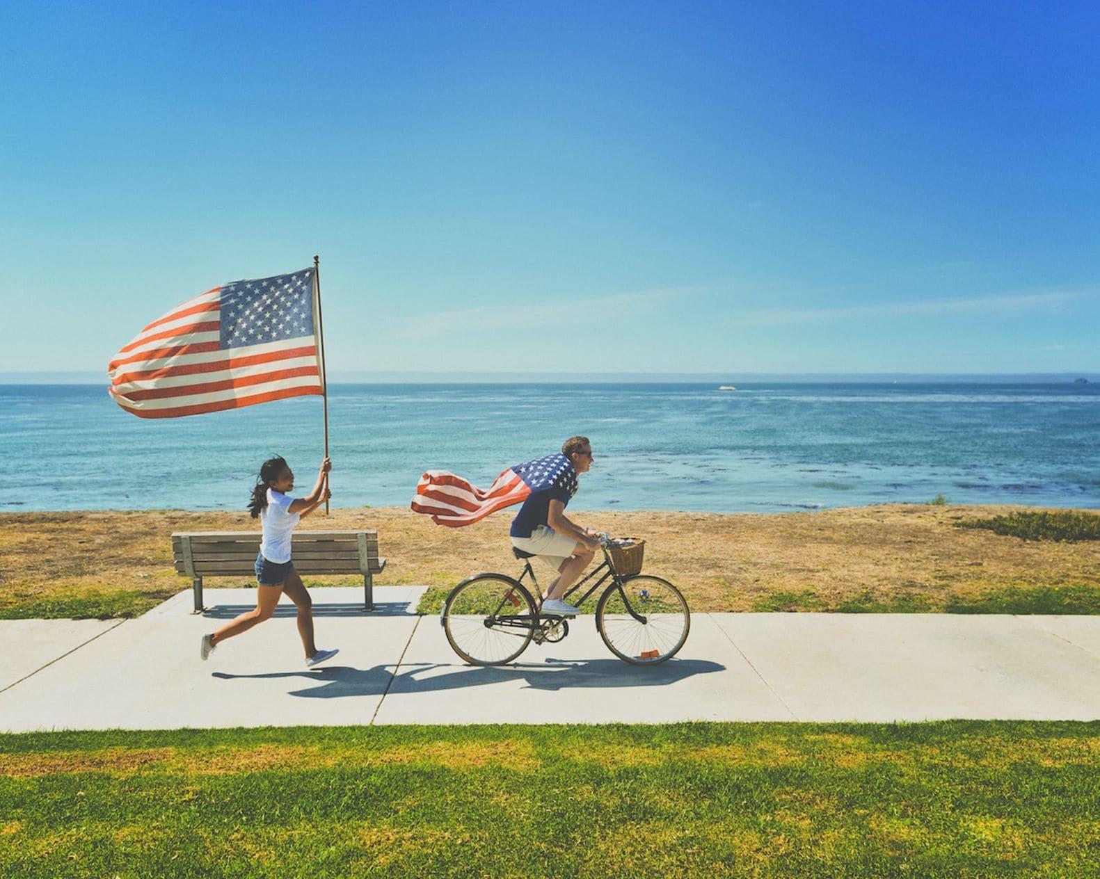 Junge und Mädchen mit USA-Flaggen am Meer
