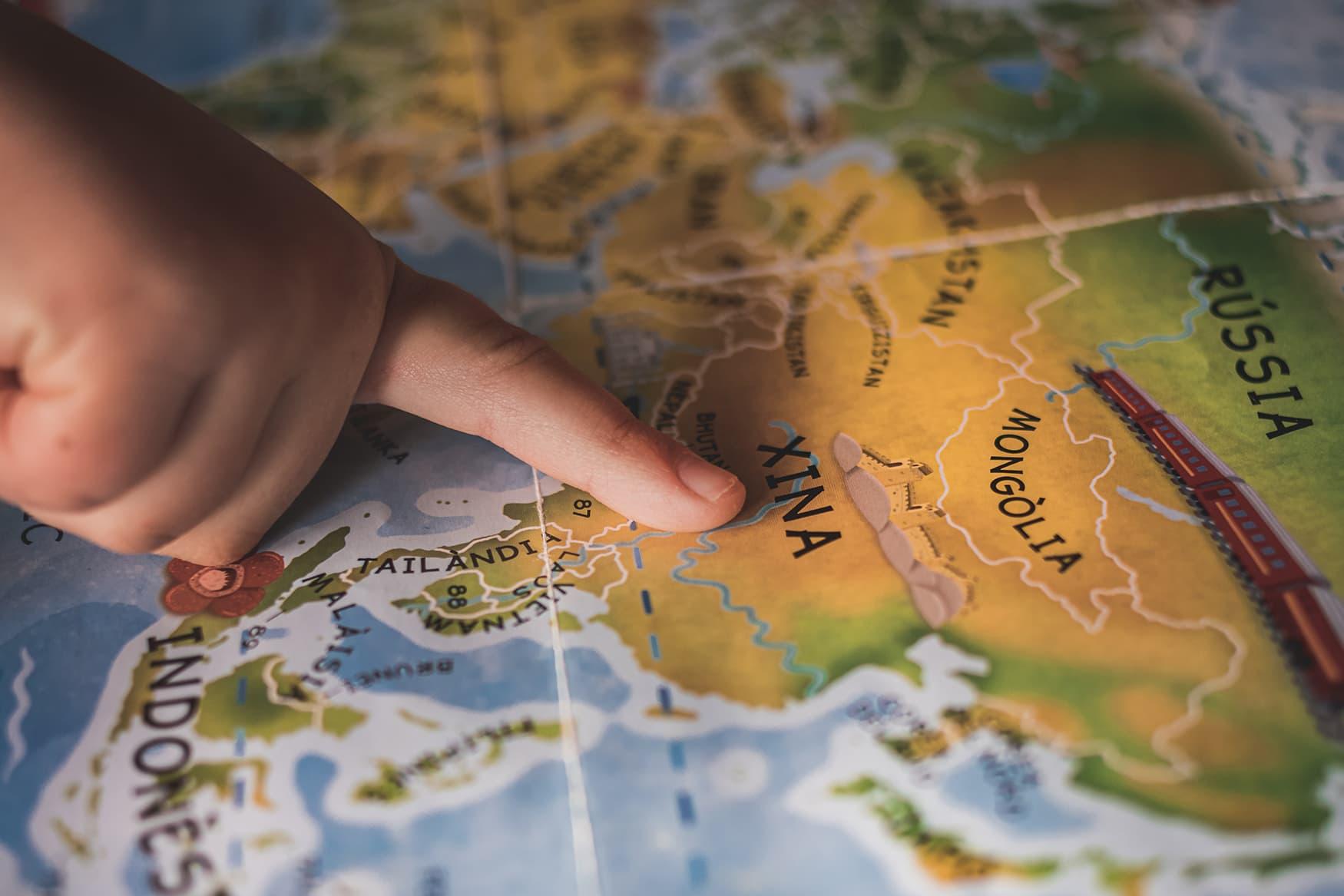 Kleiner Finger zeigt auf bunte Weltkarte