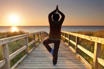 Frau beim Yoga auf Rügen während Sonnenuntergang
