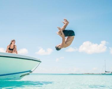 Mann macht Salto von einem Boot ins Meer im Bahamas Urlaub