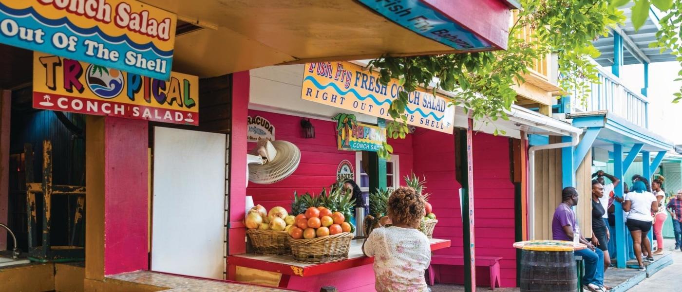Frau sitzt an Fish Fry, einem Imbiss-Stand auf den Bahamas