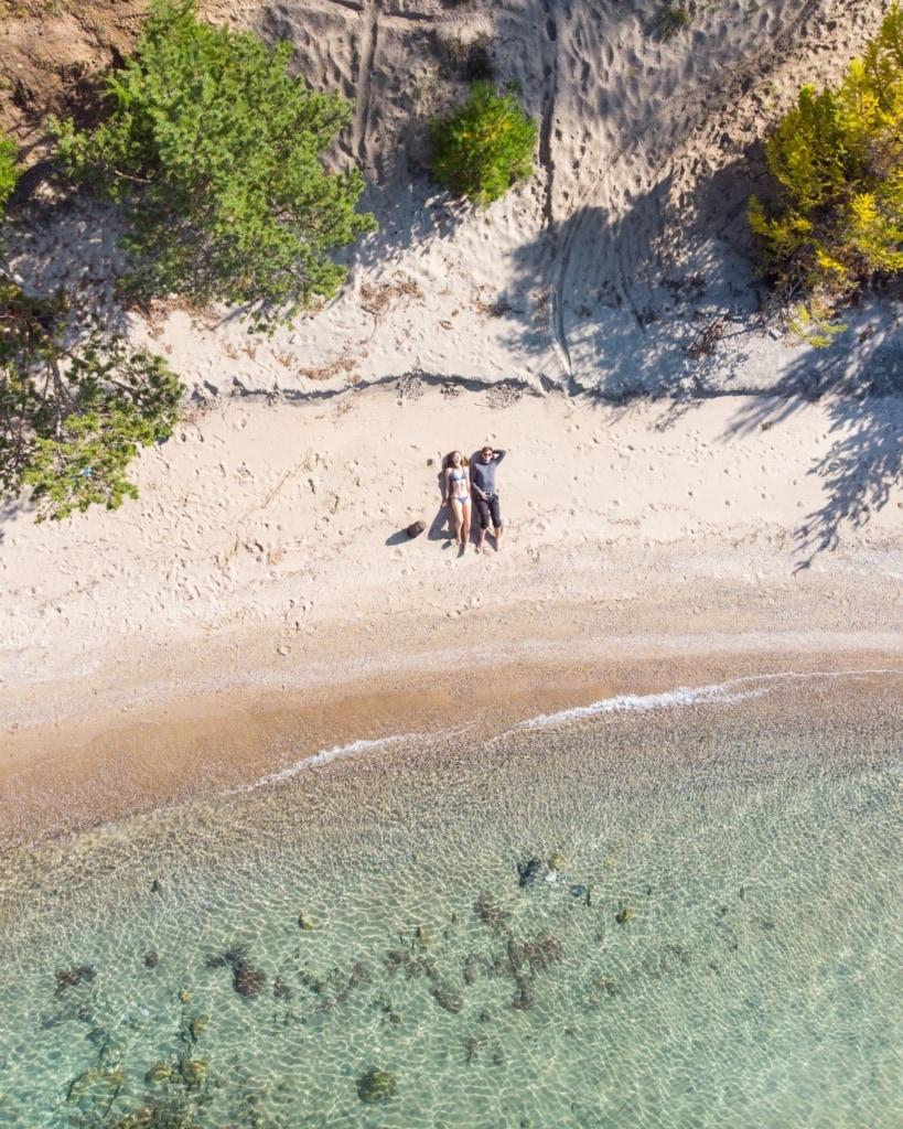 Drohnenaufnahme eines Pärchens am Strand