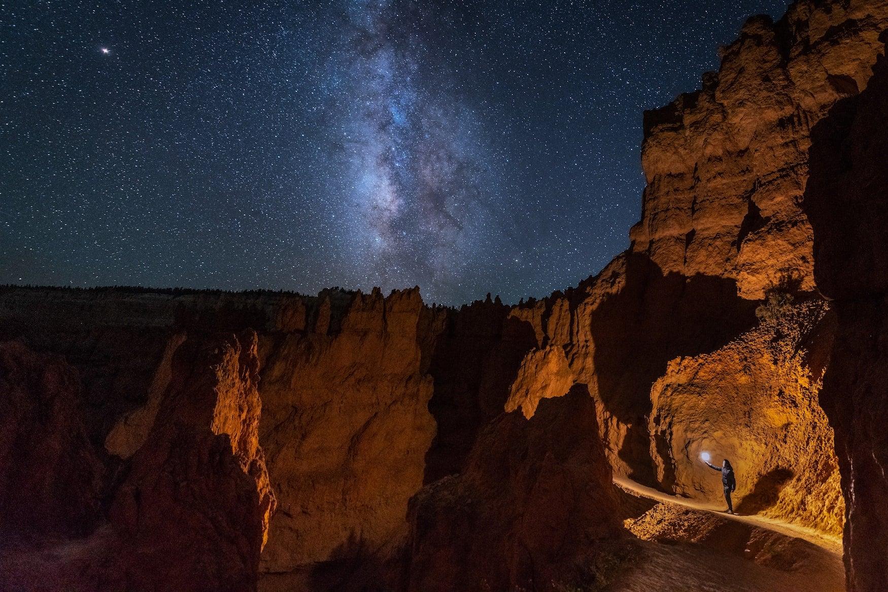 Mann mit Taschenlampe in Felsen von Bryce Canyon mit Milchstrasse
