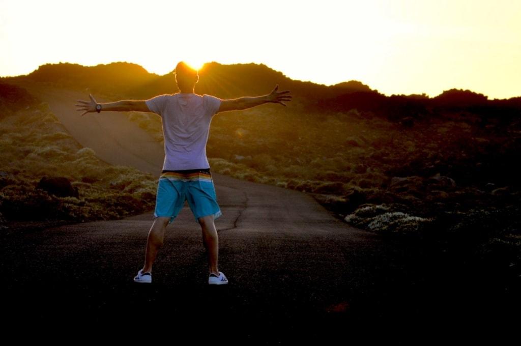 Ein junger Mann steht mit ausgebreiteten Händen auf einer Straße auf El Hierro