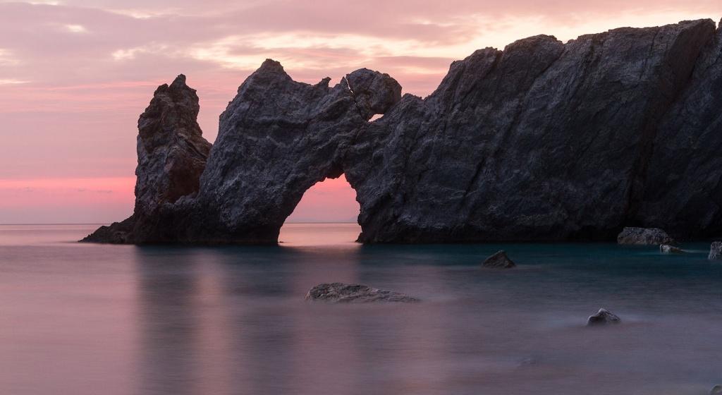 Felsbogen am Strand von Lalaria in Griechenland bei Sonnenuntergang