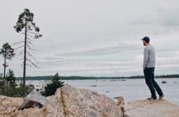 Mann steht an einem See in Finnland und blickt in die Ferne