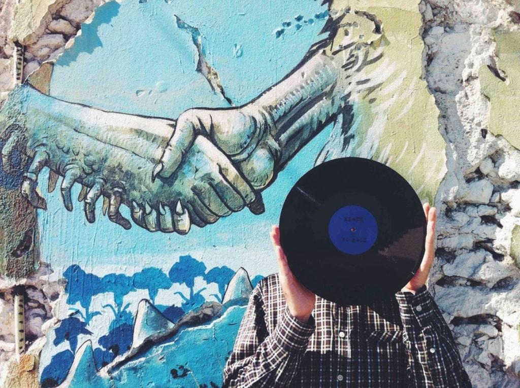 Mann vor Street-Art-Gemälde in Lissabon