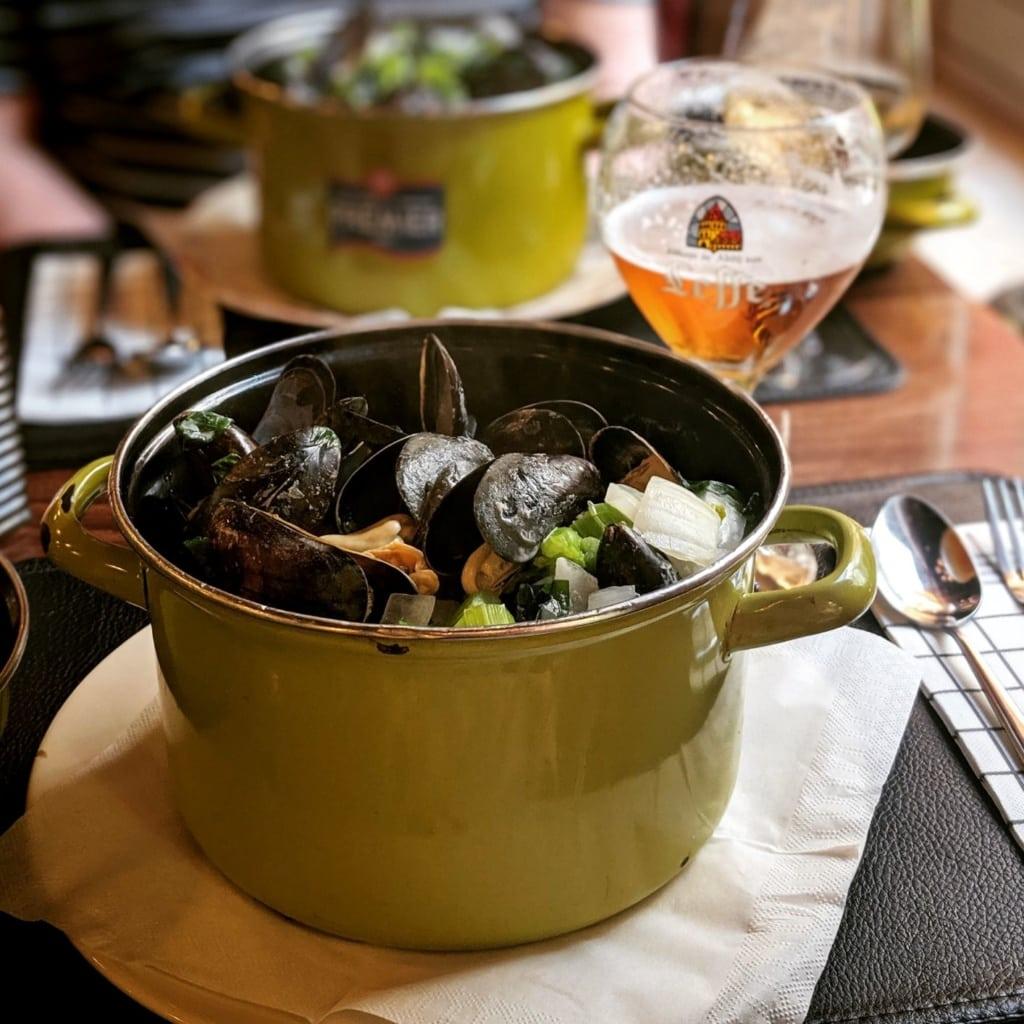 Topf gefüllt mit Muscheln, Glas Bier