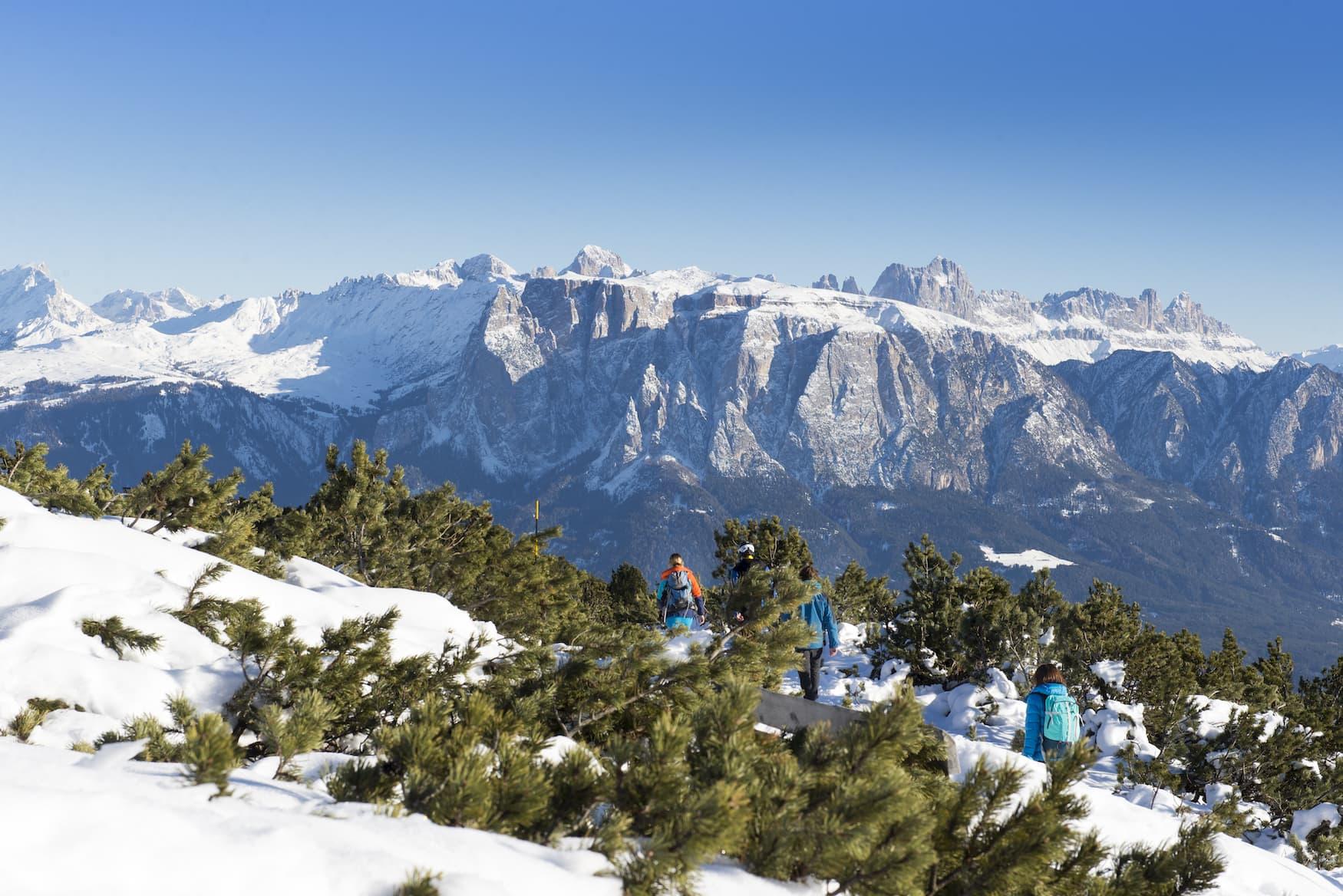 Familie wandert durch verschneite Landschaft in Ritten in Südtirol