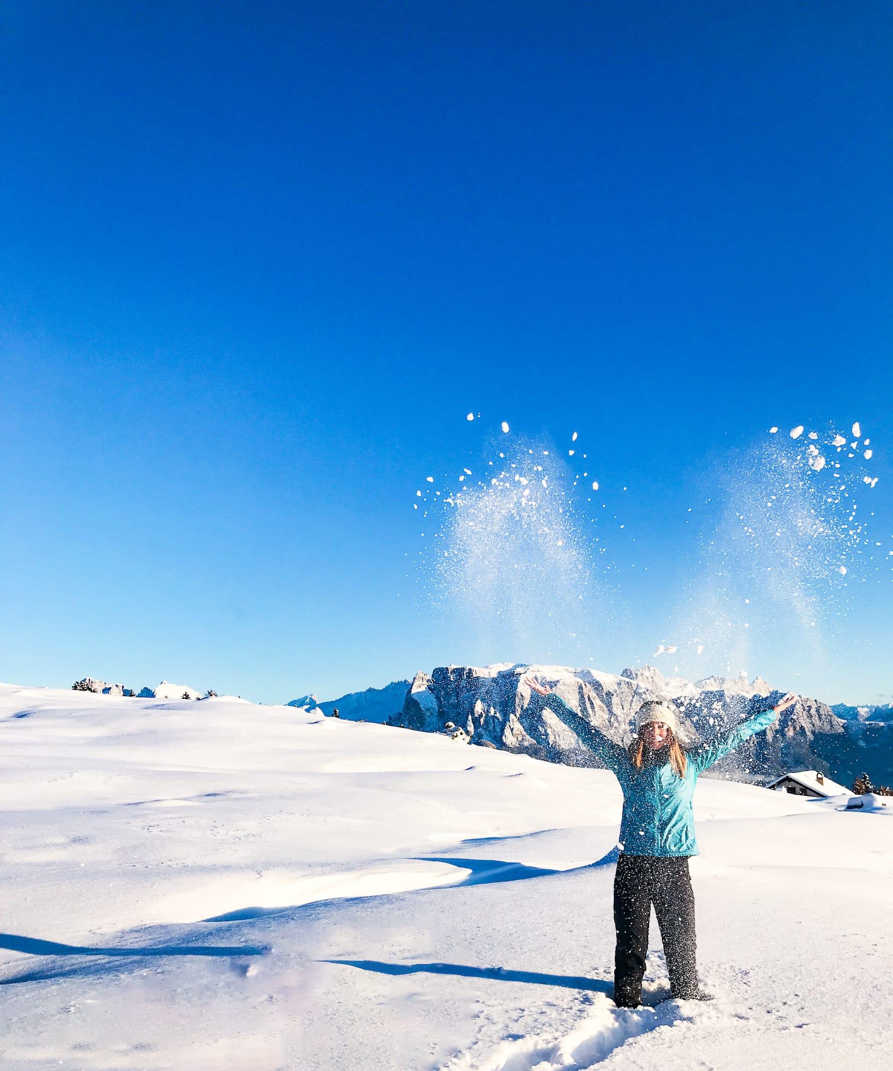 Frau wirft Arme in die Höhe in Schneelandschaft