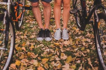 Vier Beine und Füße neben zwei Fahrrädern im Laub
