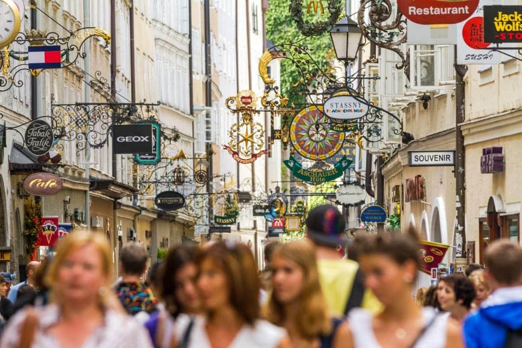 Menschen in der Getreidegasse in Salzburg über ihnen Schilder der Shops