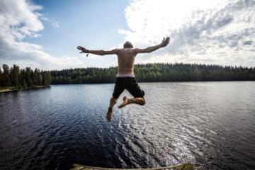 Junger Mann springt in einen See