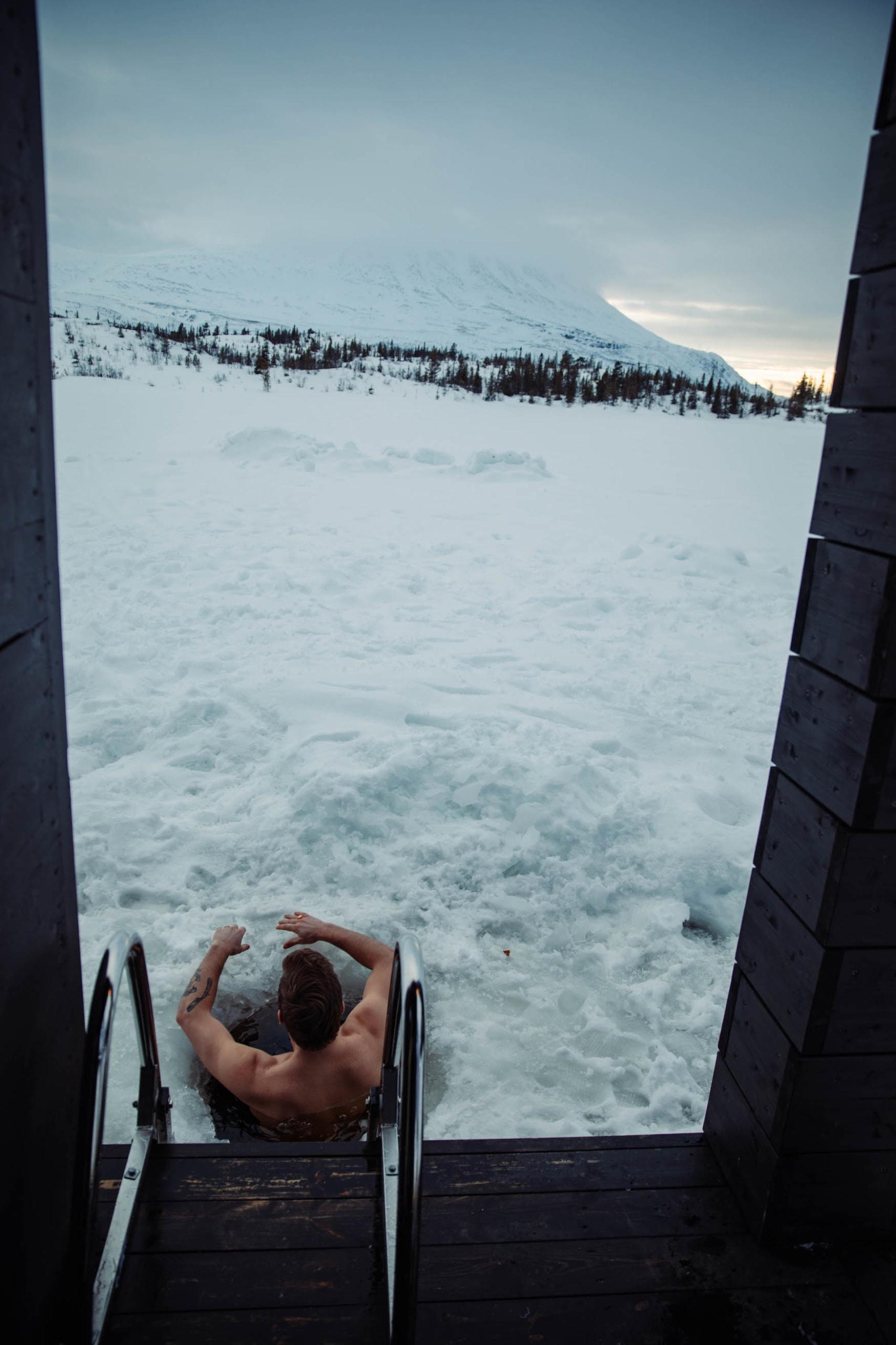 Mann nimmt ein Eisbad in verschneitem See nach Sauna