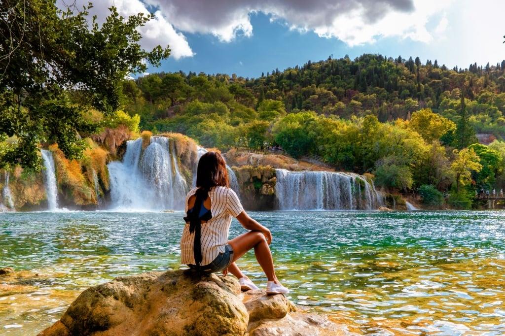 Junge Frau sitzt auf Stein und blickt auf einen Wasserfall im Nationalpark Krka, Kroatien