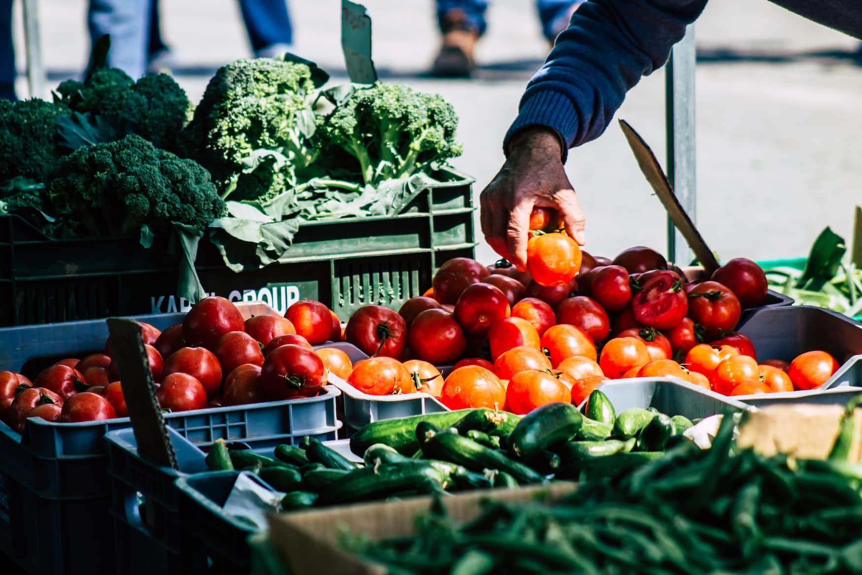 Mann schneidet Tomaten auf einem Markt in Zypern