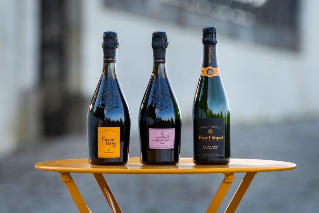 Drei Champagner-Flaschen auf einem kleinem Tisch