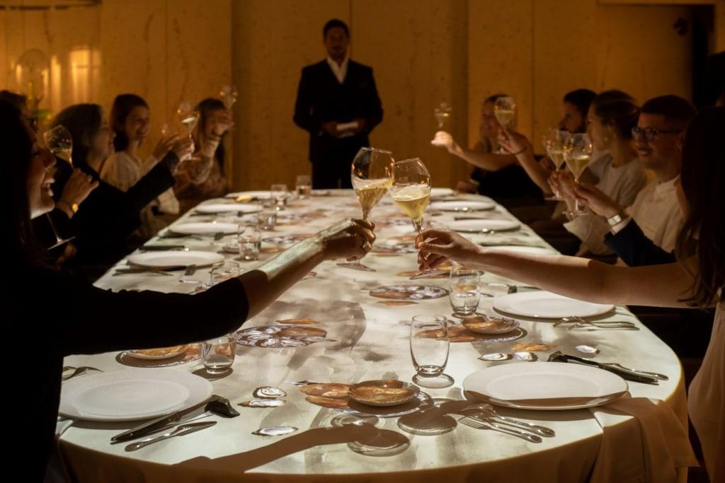 An einem ovalen Tisch sitzen rund ein Dutzend Personen und prosten sich zu