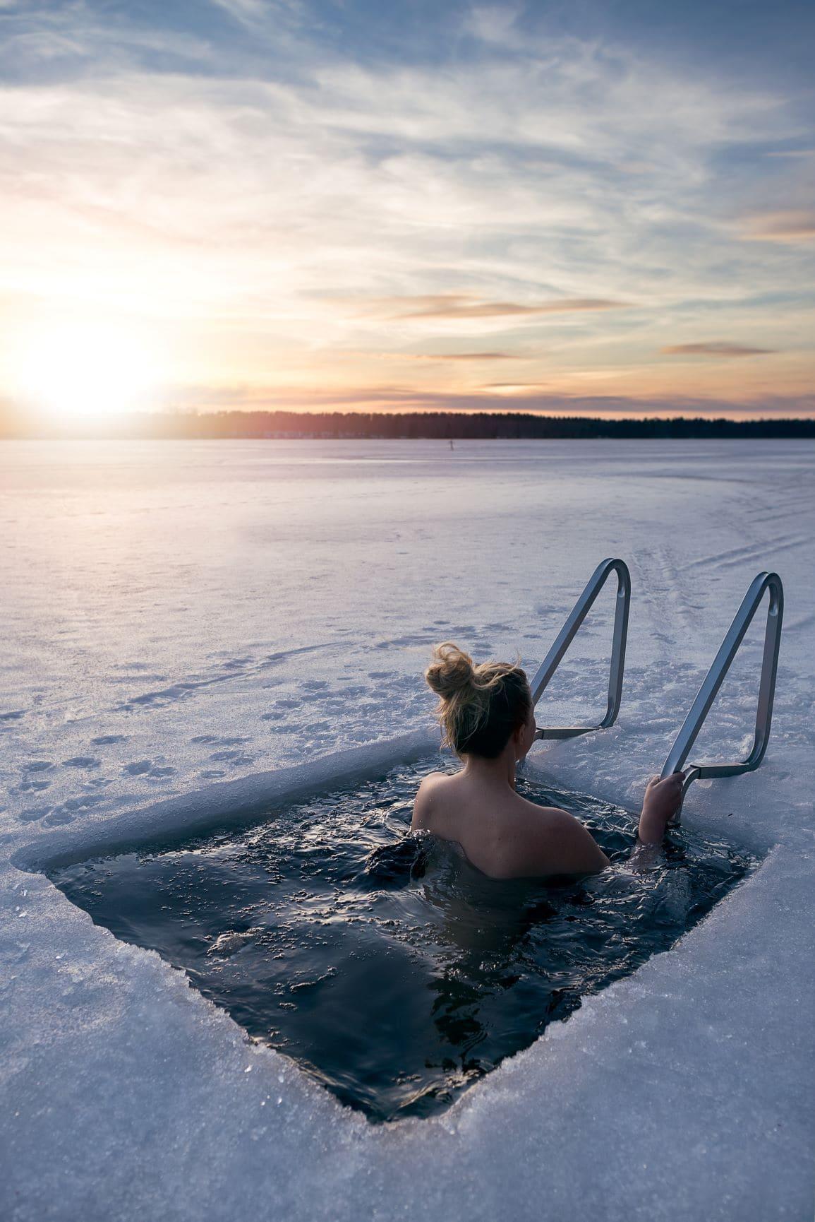 Frau nimmt Bad in Eisloch