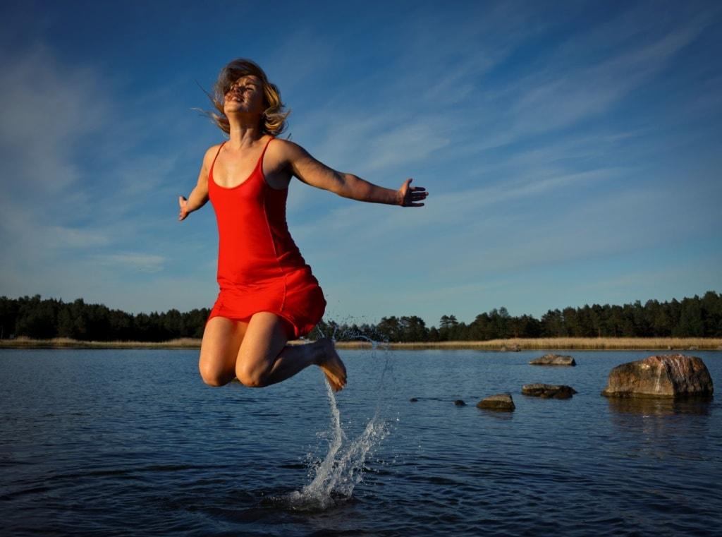 Frau macht Sprung in einem See in Finnland