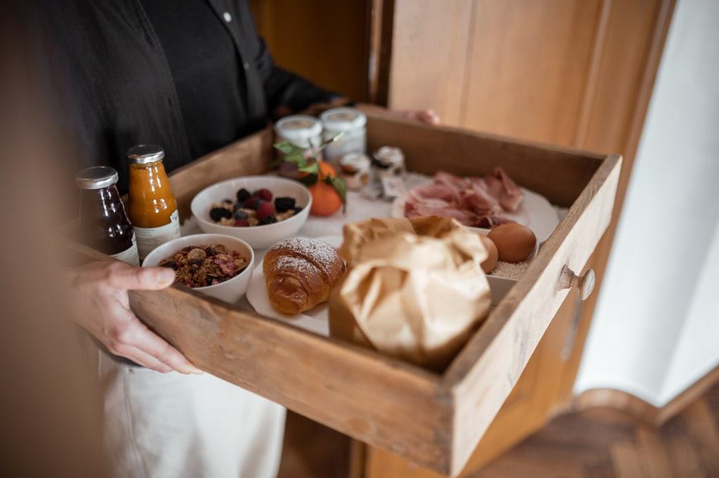 Kellner hält Schublade, die als Frühstückskorb dient