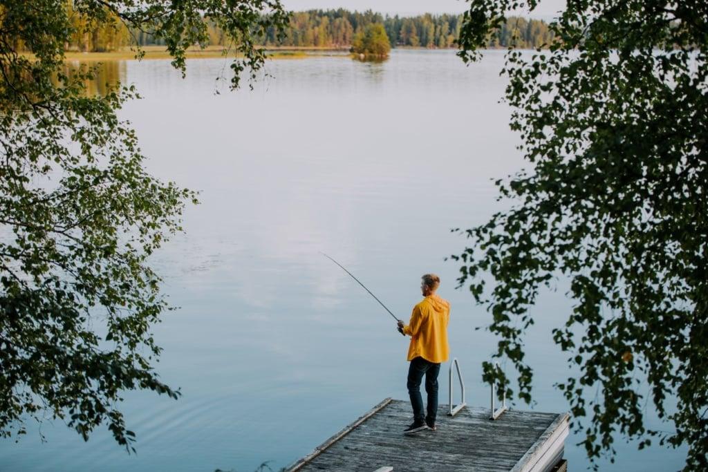 Junger Mann angelt in einem See in Finnland