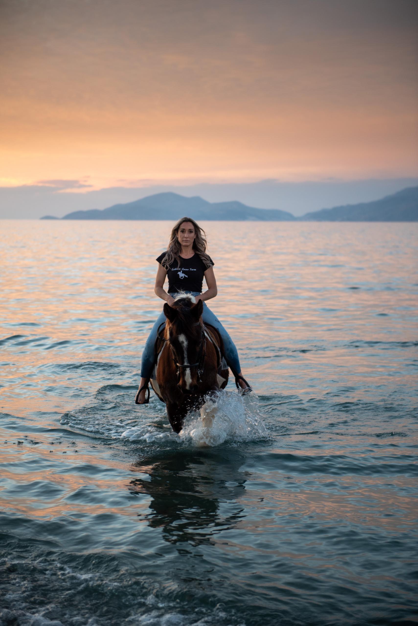 Frau sitzt auf Pferd und reitet durch Wellen bei Sonnenuntergang