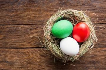Ostereier in den Farben Weiß, Grün und Rot liegen in einem Strohnest