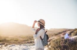 Allein reisende Frau steht in Wüste und guckt in die Ferne