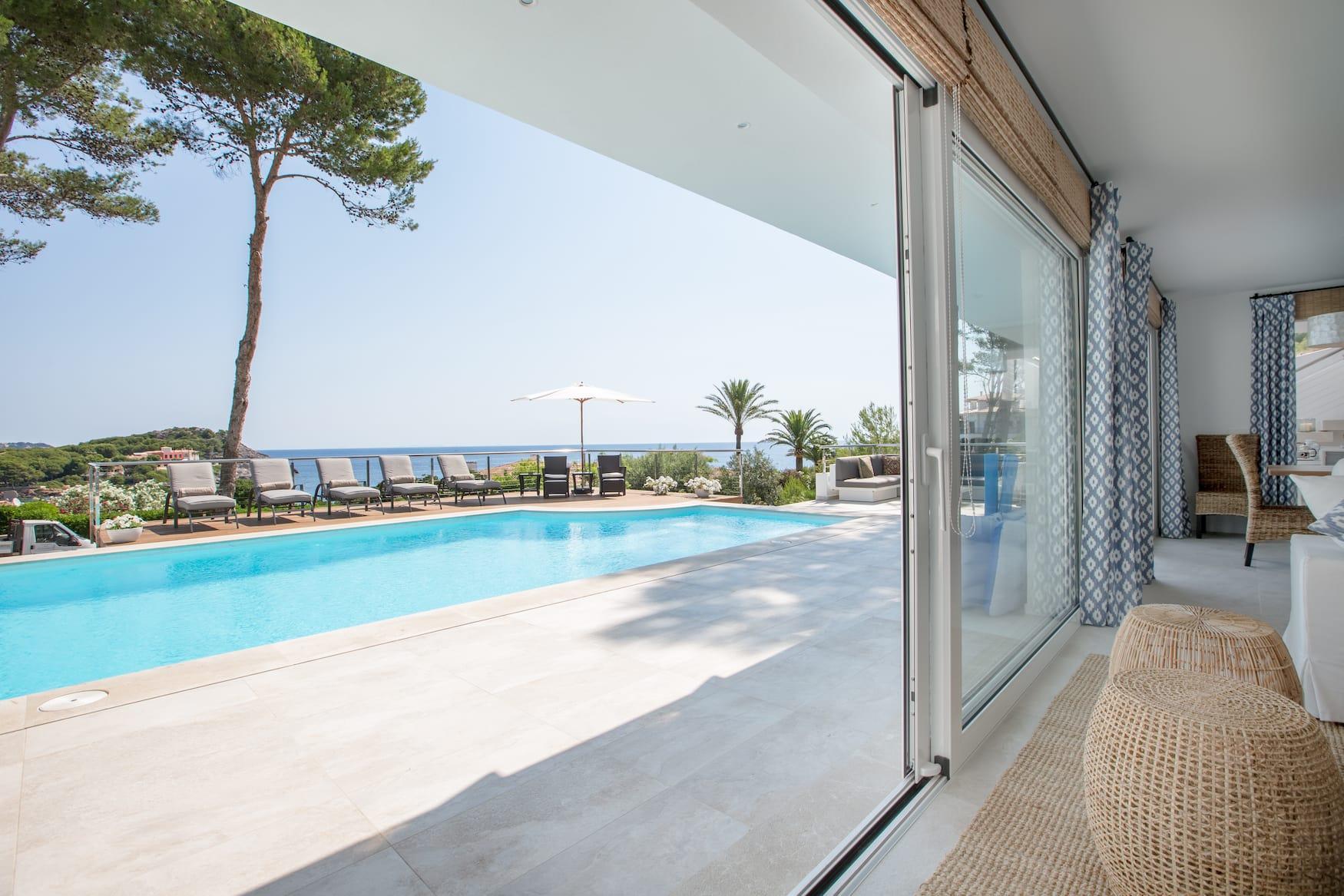 Blick aus dem Wohnraum der Brisa Marina, einem Ferienhaus auf Mallorca, auf den Pool und den dahinterliegende Ozean