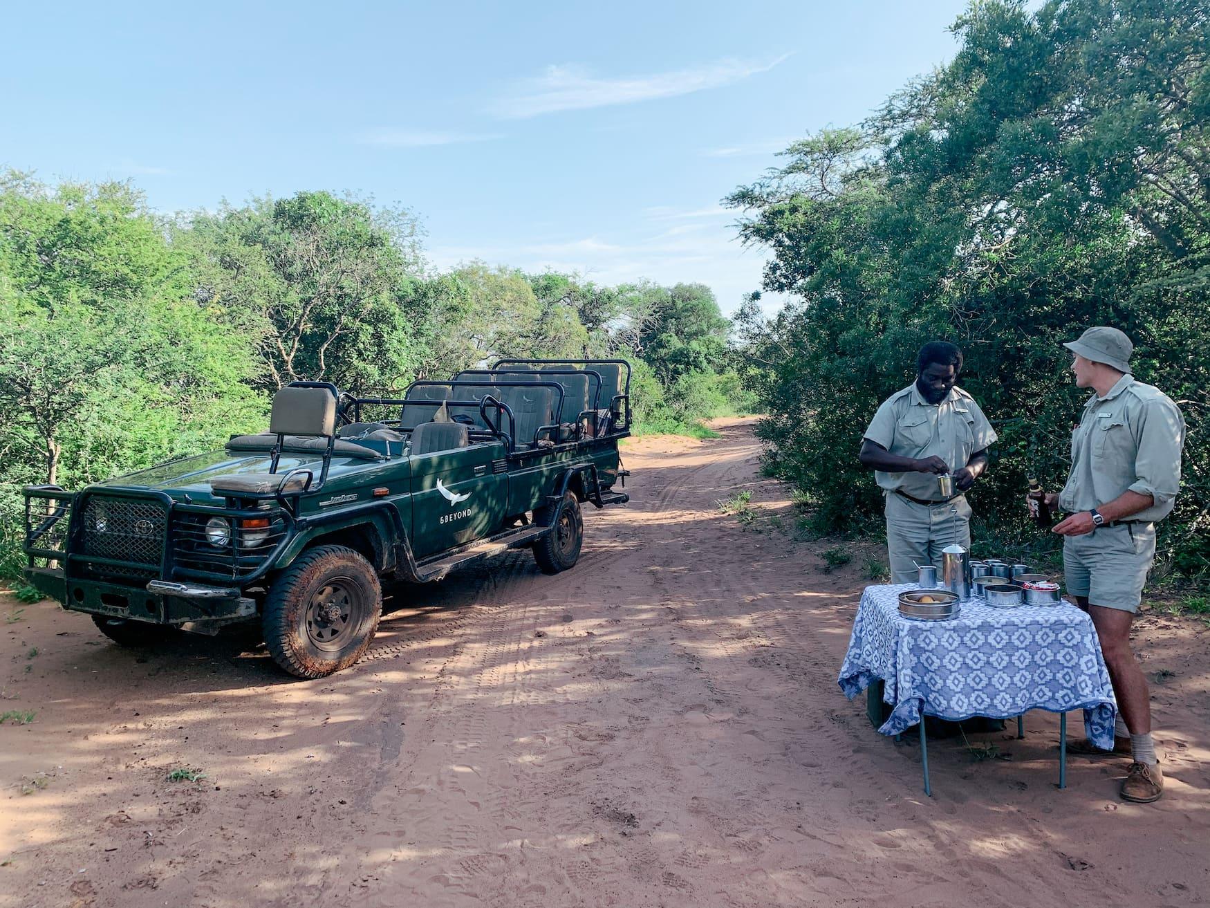 Zwei Ranger stehen an aufgebauter Bar im Busch in Südafrika
